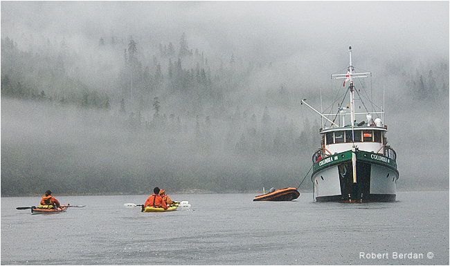 Kayakers return to the Mothership III in fog and rain by Robert Berdan ©