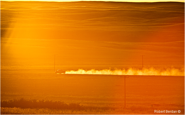Truck kicks kup dust on the prairie at sunset by Robert Berdan ©