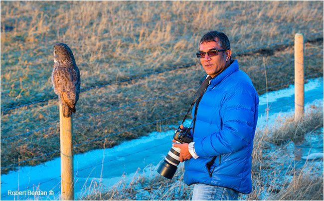 Kamal Varma standing next to a Great Gray Owl by Robert Berdan ©