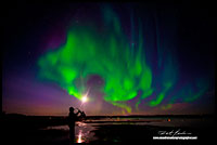 Saxophone player in front of Aurora Borealis over Yellowknife Bay by Robert Berdan