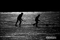 Black and white photo silhoutte of hockey players on Vermilion Lake, Banff National Park by Robert Berdan