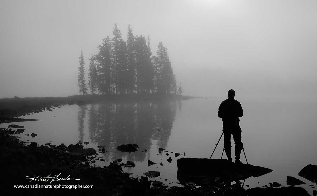 Silhouette of a photographer in front of Spirit Island before sunrise on Maligne Lake in Jasper National Park by Robert Berdan ©