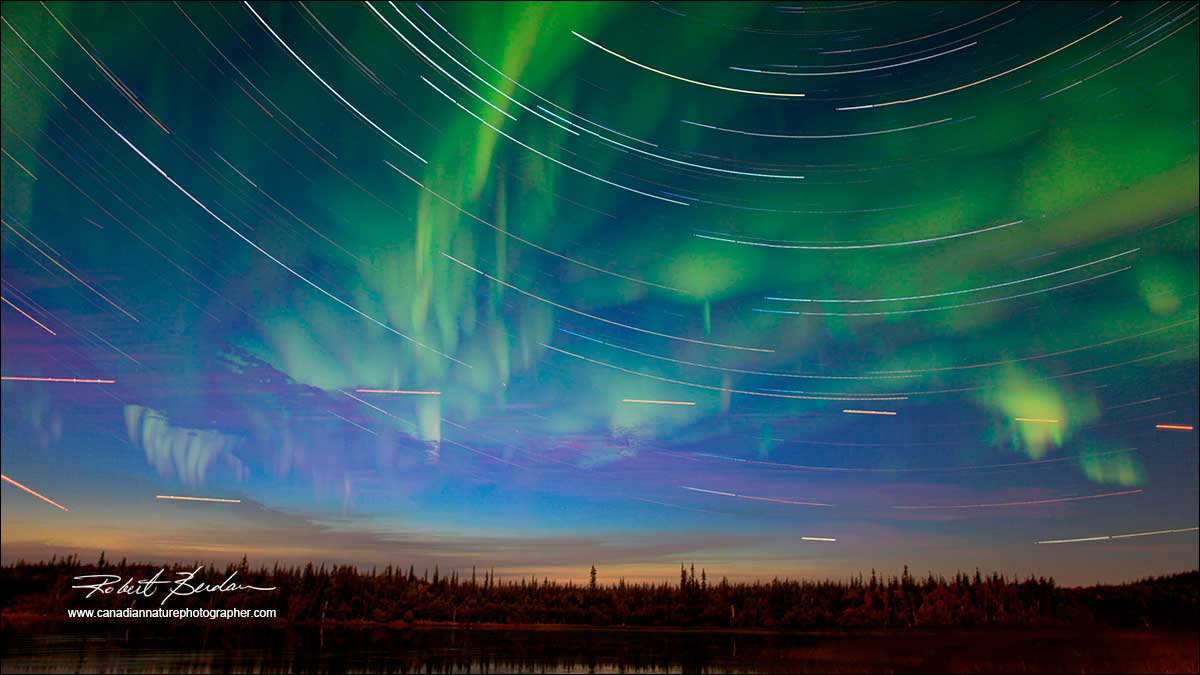 Aurora borealis and stacked images showing star trail movement by Robert Berdan