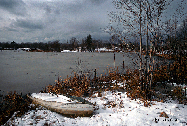 Old wooden boat on shoreline in snow by Karl Berdan ©