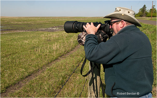 Photographer using fence post and bean bag to support his 500 mm telephoto lens by Robert Berdan ©