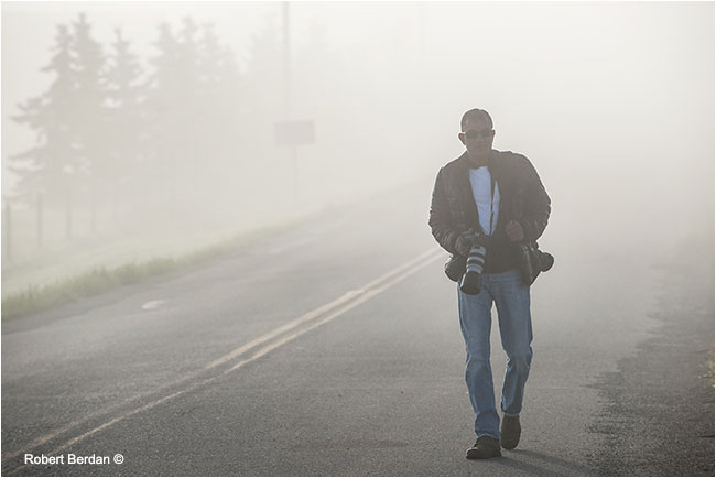 Kamal Varma walking along road in fog by Robert Berdan