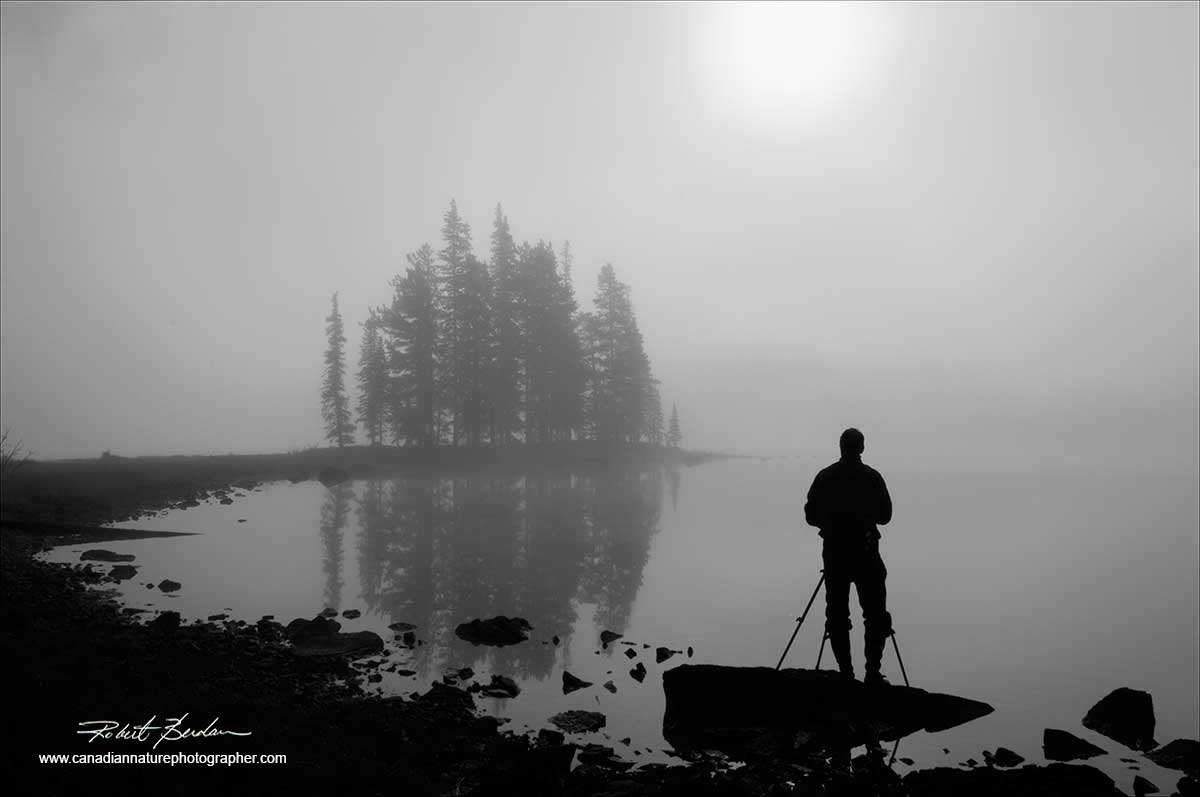 Black and white photo of photographer in front of Spirit Island, Jasper National Park by Robert Berdan ©