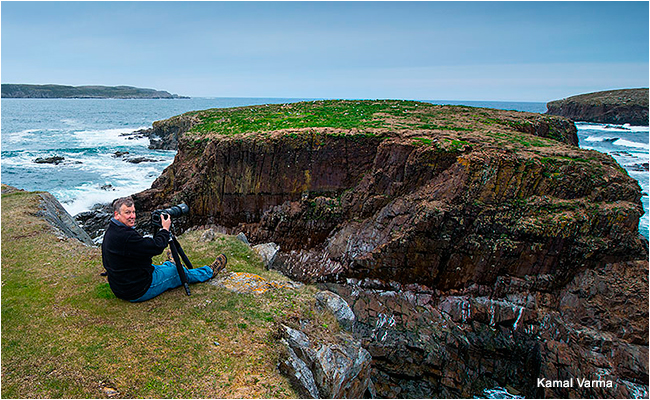 Photographer sitting across from Bird Island Newfoundland in order to photograph Breeding puffins by Kamal Varama