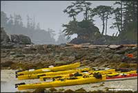 Kayaks on shore line of outer island group off coast of British Columbia by Robert Berdan